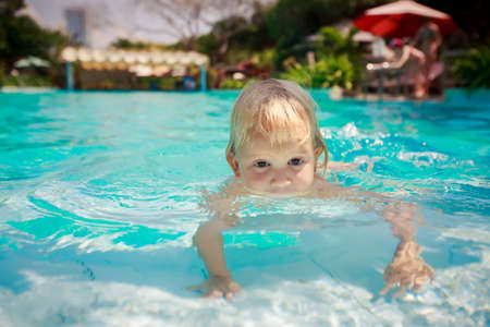 exotic gleam: closeup small blonde girl walks on hands in shallow transparent water of hotel swimming pool