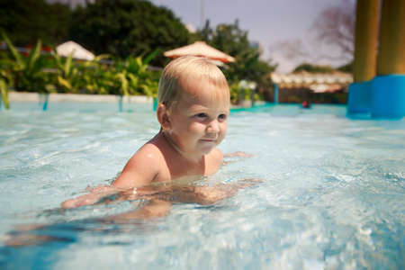 exotic gleam: small blonde girl bathes smiles and plays in hotel swimming pool against tropical plants Stock Photo