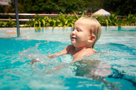 exotic gleam: closeup portrait small blonde girl stands smiles and looks into water in hotel swimming pool against tropical plants Stock Photo