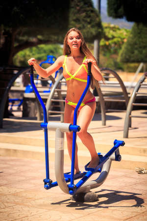 simulator: young blonde longhaired slim girl in bikini stands on stepper simulator on park sports ground against tropical plants Stock Photo