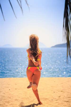 hands behind back: blonde slim female gymnast in bikini backside runs to sea hands behind back against palm branch wind shakes long hair