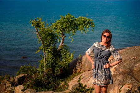 frock: young brunette girl in short grey frock with lace and sunglasses stands on rock near tropical plant against azure sea Stock Photo