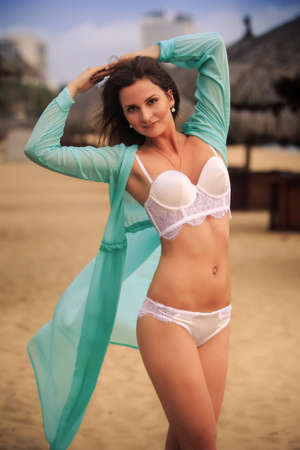 frock: closeup brunette slim girl in white underwear and frock stands hands over head smiles against blurry beach umbrellas