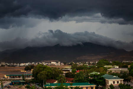 upper panorama of resort city with dark grey cumulus thunderclouds above city and mountains