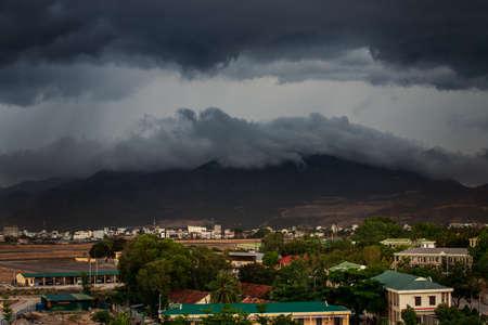 街と山の上の暗い灰色積雲雷雲とリゾート都市のパノラマ コース上部