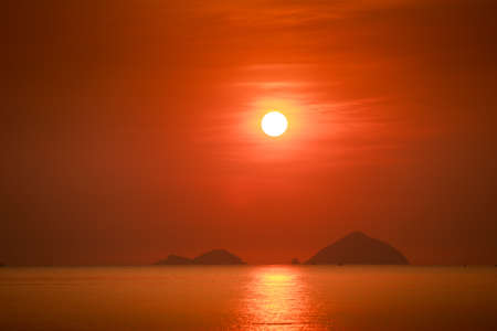 path to romance: white disk of large sun among red sky above sea with sun path and islands at sunrise