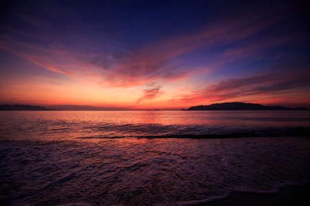 fleecy: panorama of fantastic beautiful dark blue and red sky with fleecy clouds before sunrise and sea on foreground