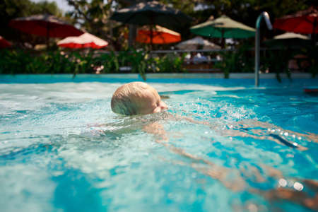 screwed: closeup head of small blonde girl with screwed up eyes almost full in water of pool against colourful parasols