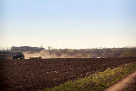 operates: tractor cultivator on big wheels operates on ploughed field raises dust against countryside ground road on foreground