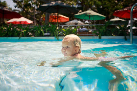 exotic gleam: closeup small blonde girl swims in shallow transparent water of hotel swimming pool against colourful shade parasols