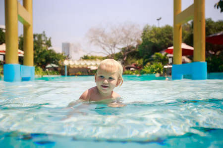 exotic gleam: closeup small blonde girl stands in shallow water of hotel swimming pool points to something against yellow pillars Stock Photo
