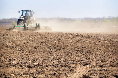 ploughed: backside view tractor cultivator on big wheels raises great dust on ploughed ground