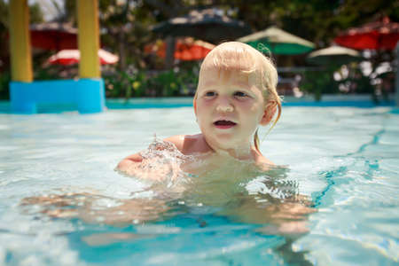 exotic gleam: closeup small blonde girl squats speaks in shallow transparent water of hotel swimming pool against colourful parasols