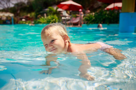 exotic gleam: small blonde girl stands on fours in shallow transparent water of hotel swimming pool looks slyly against parasols