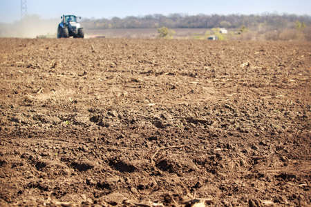 operates: distant tractor cultivator on big wheels operates and raises great dust with ploughed soil on foreground