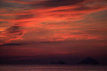 exotic gleam: panorama of fantastic beautiful red fleecy clouds before sunrise and sea on foreground