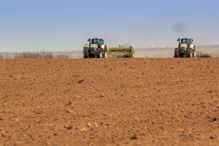 panorama of two operating tractors in field and brown soil on foreground