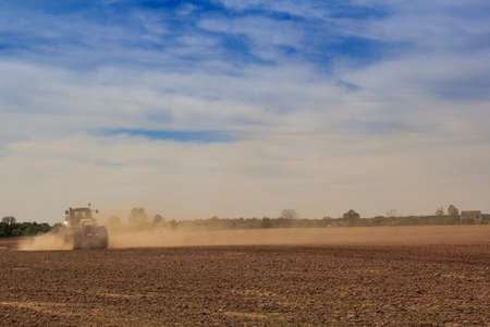 fleecy: fantastic blue sky with fleecy clouds above ploughed field and distant tractor in great dust cloud in spring