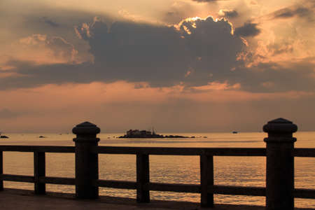 barrier island: panorama of sunrise from behind golden cumulus clouds taken from embankment barrier against sea and island
