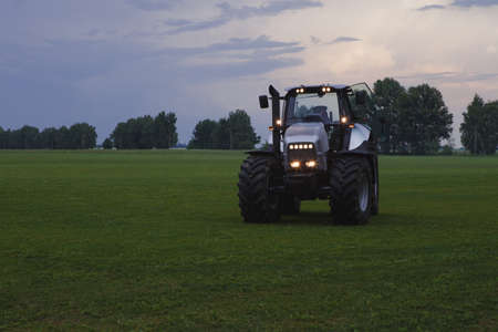 agro: agro tractor with bright head lights in green field at background of trees at dusk Stock Photo