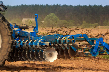 cultivator: cultivator stands on ground road by ploughed field against village and forest