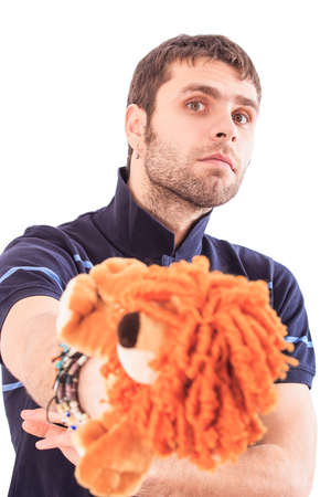 ear ring: handsome bearded light brown-haired european guy with ear-rings holds in hands soft animal lion toy crosses arms