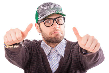 ear ring: handsome bearded european guy in base-ball cap glasses and in ear-rings shows thumbs and makes faces
