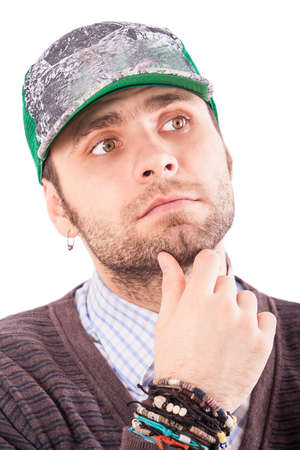 touch base: portrait of handsome bearded european guy in base-ball cap with ear-rings touches chin looks upward