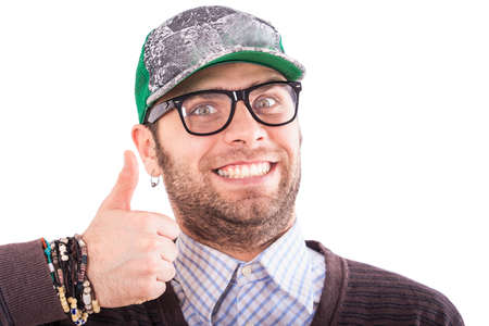 ear ring: portrait of handsome bearded european guy in base-ball cap glasses and in ear-rings shows thumb and teeth Stock Photo