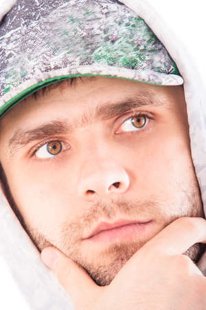 hoody: closeup handsome bearded european guy in grey hoody and base-ball cap makes serious face touches chin Stock Photo