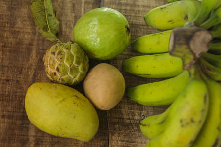 sweetsop: closeup picture of ripe green sugar-apple guava mango banana and sapodilla on ripped brown wooden table background Stock Photo