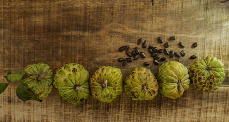 sweetsop: top view picture of sweet-sop dark seeds near nice unbroken ripe sugar-apples on wooden table background