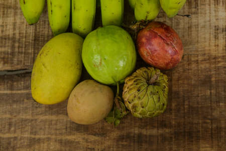 sweetsop: top view of closeup fruits set of ripe green sugar-apple guava mango banana passion-fruit and sapodilla on ripped brown wooden table background