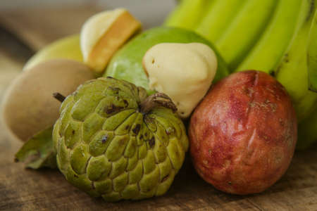 sweetsop: closeup ripe green sugar-apple guava mango passion-fruit and sapodilla against banana on ripped brown wooden table background