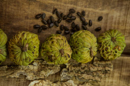 sweetsop: top view picture of sweet-sop brown seed by unbroken ripe sugar-apples on wooden table background