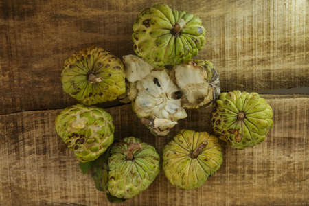 unbroken: top view still-life of broken ripe sugar-apple with brown seed and unbroken ripe sugar-apples on wooden table background
