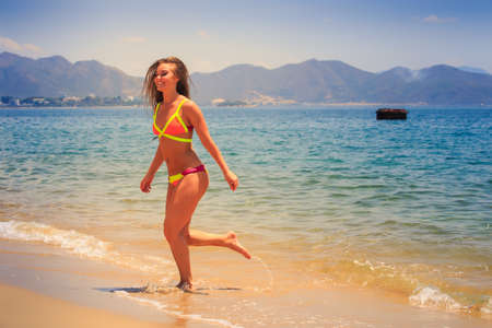 blonde longhaired slim female gymnast in bikini runs out of sea water to beach and laughs against hills Stock Photo