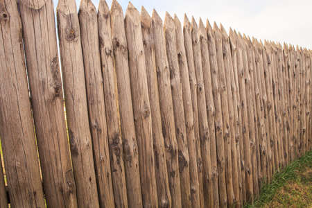 palisade: high old wooden fence of logs in form of palisade vanish into space in countryland