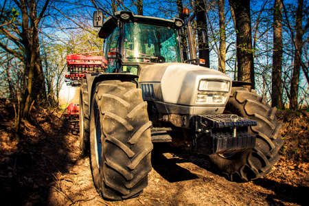 cultivator: closeup tractor cultivator on big wheels on natural soil road in spring forest Stock Photo