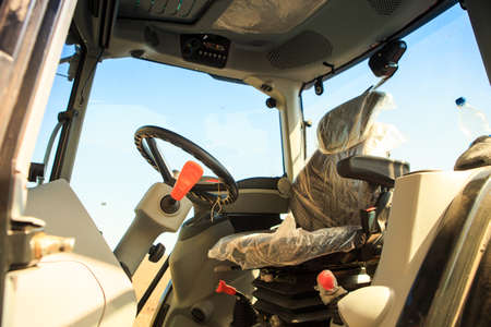 cultivator: interior view of cultivator tractor cabin with steering wheel under bright sunlight