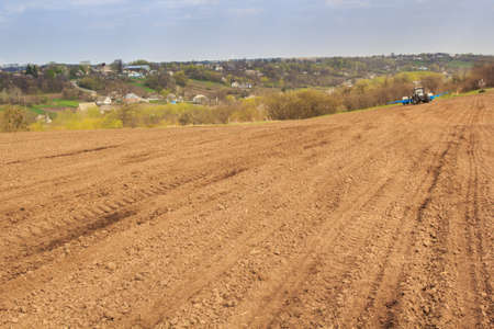 the ploughed field: tractor in brown ploughed field in idyllic spring against distant forest and Ukrainian village on hills
