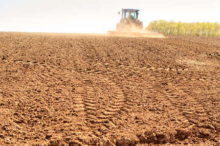 cultivator: distant tractor cultivator leaves fresh track on wet brown ploughed field against far forest Stock Photo