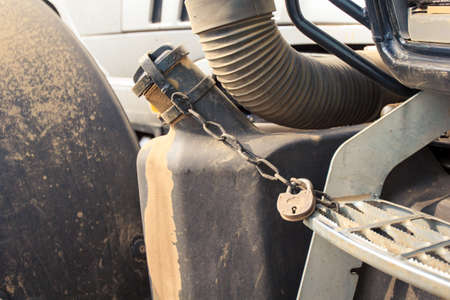 cultivator: closeup petrol tank of cultivator tractor with pad-lock and chain Stock Photo