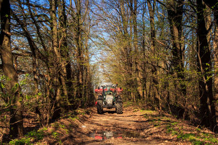 cultivator: tractor cultivator on big wheels on natural soil road in spring forest against blue sky Stock Photo
