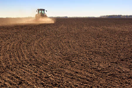 operates: distant cultivator on big wheels operates on large ploughed field raises dust behind