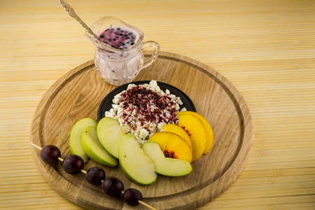 white yogurt in small glass and cottage cheese with acai powder decorated with sliced apple and peach on wooden plate on table background