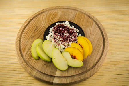 cottage cheese with acai powder decorated with sliced apple and peach on wooden plate on table background Stock Photo