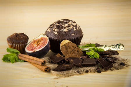closeup chocolate muffins, black chocolate, figs, cinnamon sticks, green mint and superfood cacao powder lie on the light wooden background Stock Photo