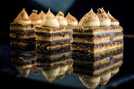 黒い鏡の背景に白いクリームで飾られた3つのチョコレートオペラケーキのスライス