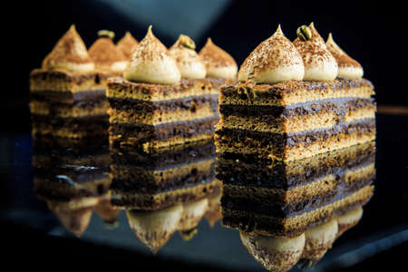 three chocolate opera cake slices decorated with white cream on black mirror background
